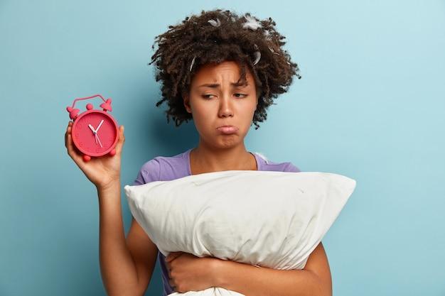 Молодая брюнетка женщина с перьями в волосах держит подушку и будильник