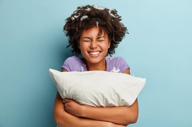 Молодая брюнетка женщина с перьями в волосах, держа подушку