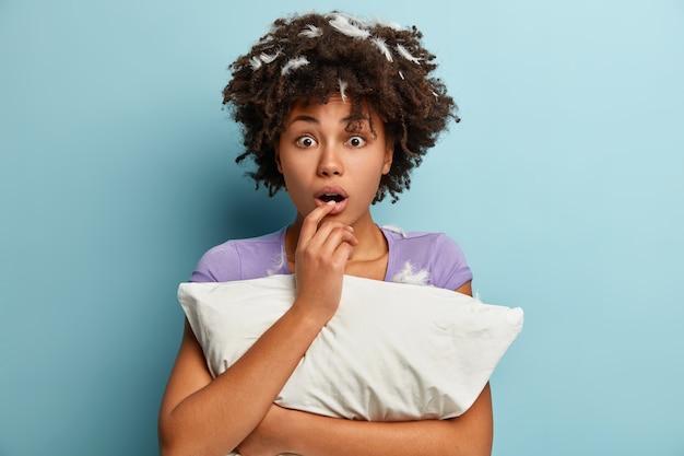 枕を保持している髪の羽を持つ若いブルネットの女性