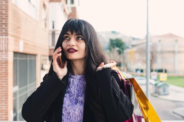 買い物の後に電話をかける長い髪と緑色の目を持つ若いブルネットの女性。ショッピングバッグ。ガーネット塗装の唇。ショッピングの概念。