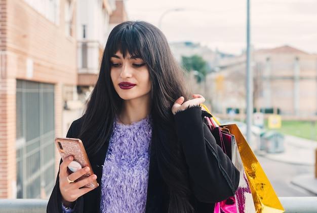 買い物の後に彼女の携帯電話を使用して長い髪と緑色の目を持つ若いブルネットの女性。ショッピングバッグ。ガーネット塗装の唇。ショッピングの概念。