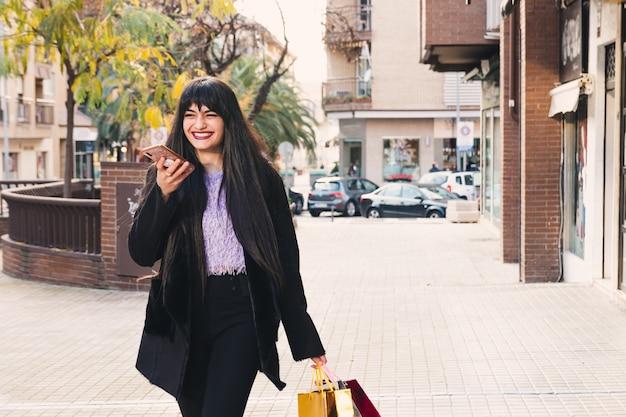 長い髪と緑の目を持つ若いブルネットの女性が買い物袋を持って歩いています。笑顔。ショッピングのコンセプト。