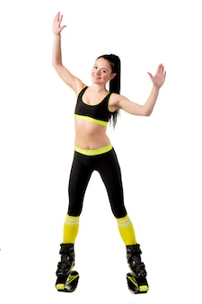 Young brunette woman with long hair training in a kangoo jumps shoes.