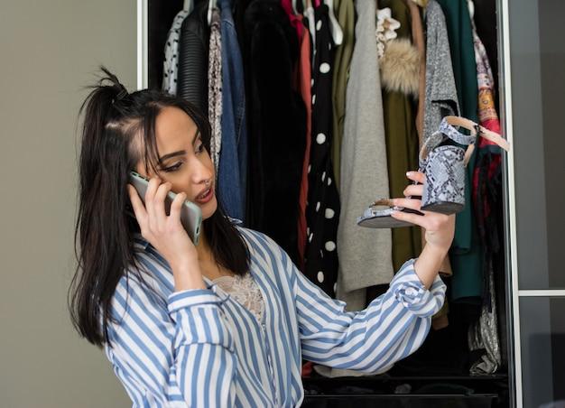 메이크업 그녀의 옷장에서 옷을보고 어떤 신발을 착용할지 결정 젊은 갈색 머리 여자. 휴대폰에서 말하고 있습니다.