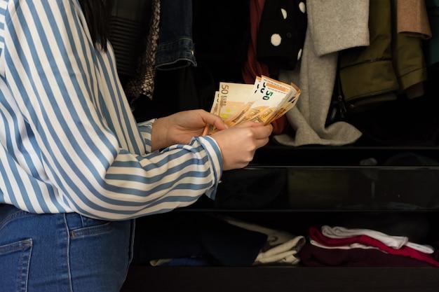 彼女のワードローブの服を見て、どの服を買うべきかを考えているメイクアップの若いブルネットの女性。節約されたお金を数える。コンセプトシューズとレディースファッション。