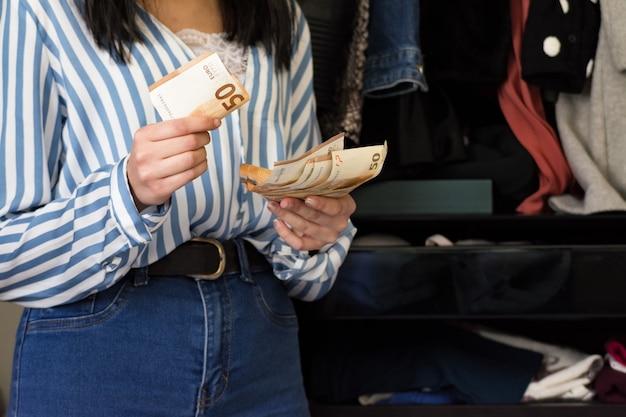 메이크업 그녀의 옷장에있는 옷을보고 구매할 옷에 대해 생각 하 고 젊은 갈색 머리 여자. 저축 된 돈 계산. 컨셉 슈즈와 여성 패션.