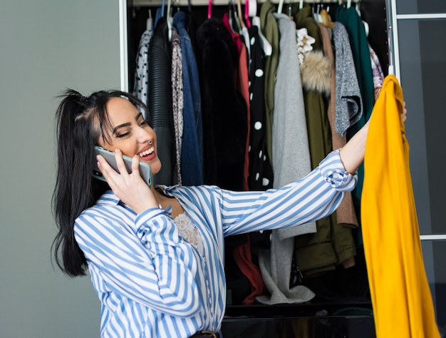 Young brunette woman with make-up looking at the clothes in her wardrobe and deciding which shoes to wear. speaking at the cellphone.