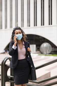Young brunette woman with medical mask having a phone conversation outdoors. business concept.