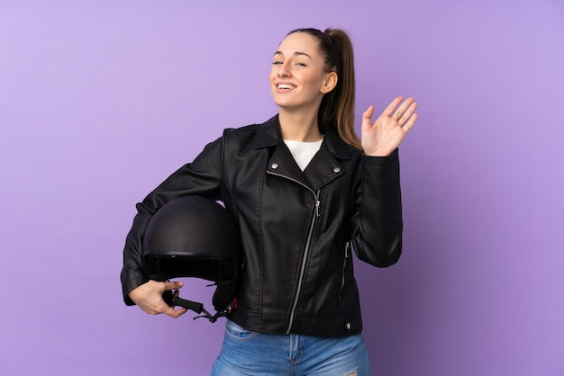 Young brunette woman with a motorcycle helmet over isolated purple wall saluting with hand with happy expression
