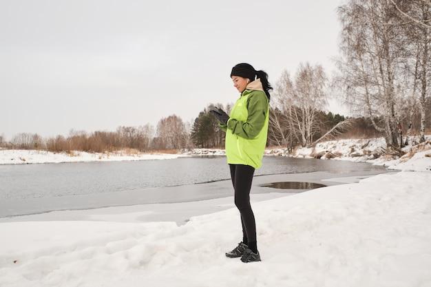 Молодая брюнетка женщина с хвостиком стоит у реки и анализирует беговой маршрут на смартфоне