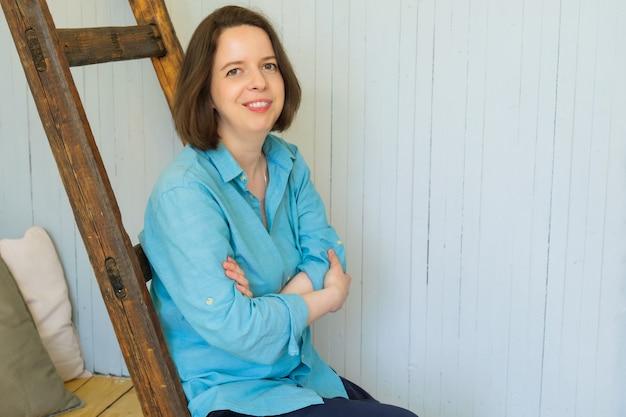 Молодая брюнетка женщина с волосами до плеч, улыбаясь дружелюбно. женщина в ярко-синей рубашке сидит на деревянной стремянке, скрестив руки на груди. место для текста справа.