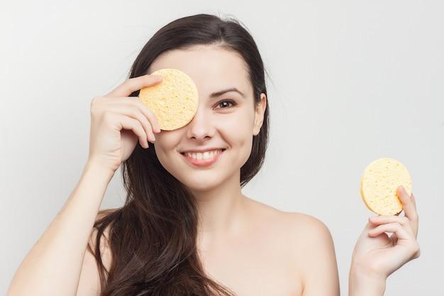 皮膚を浄化するスポンジで若いブルネットの女性