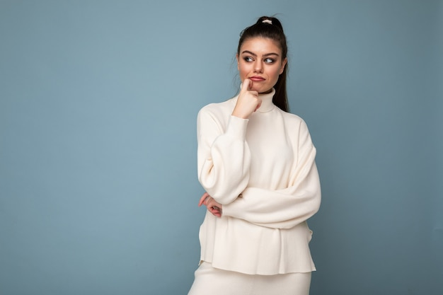 腕を組んで、あごに手を上げてカメラを自信を持って見える青い背景の上に分離された白いカジュアルセーターを着ている若いブルネットの女性。前向きに考える。