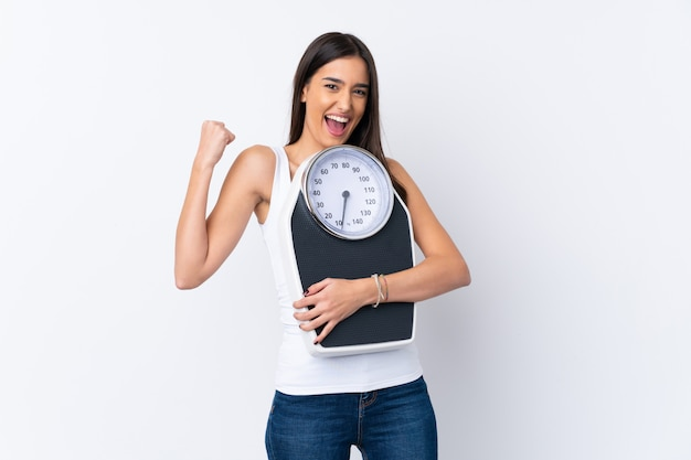 Young brunette woman with weighing machine and doing victory gesture