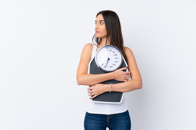 Young brunette woman with weighing machine and looking side