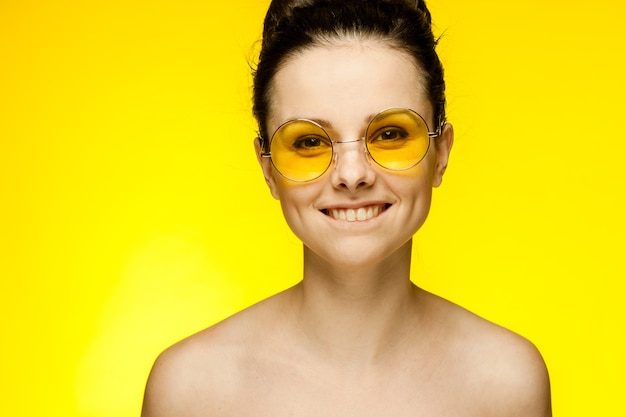 Young brunette woman in yellow glasses