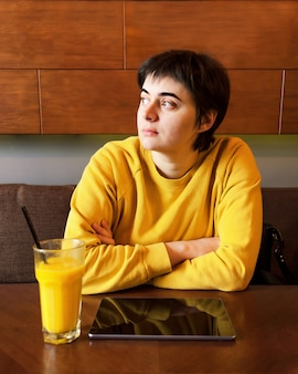 Young brunette woman in yellow hoodie at table with glass of mango smoothie and tablet