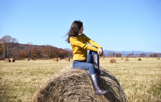 Young brunette woman in yellow sweater and rubber boots sitting on top of haystack in field