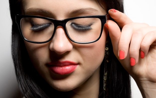 Young brunette womans face with extended lashes in glasses touching eyeglass frame over white background in photo studio