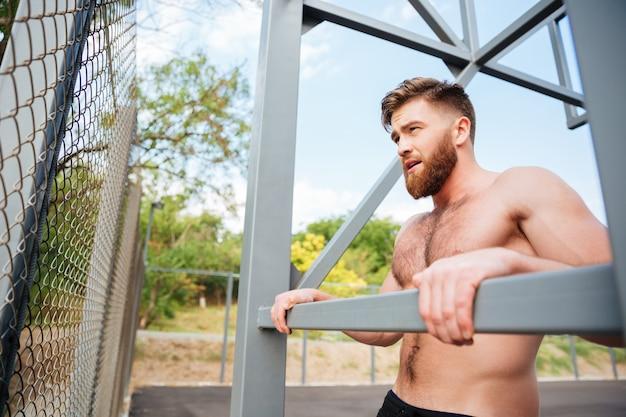 Молодой брутальный бородатый сильный мужчина делает спортивные упражнения на открытом воздухе