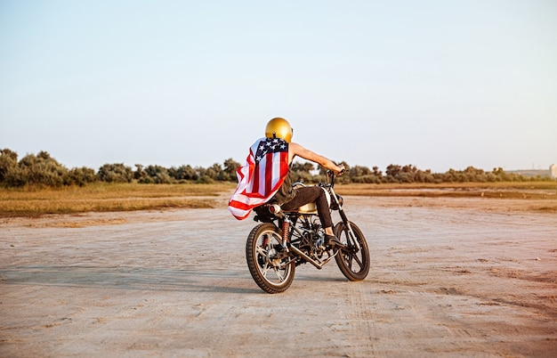 Young brutal man in golden helmet and american flag cape driving retro motorcycle
