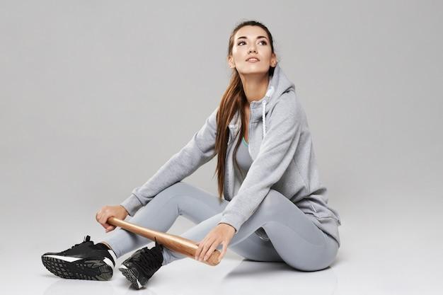 Молодая зверская sportive женщина в sportswear сидя с битом на белизне.