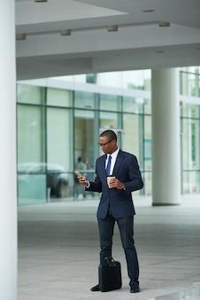 空港ターミナルの外に立って、コーヒーを飲み、タクシーを注文するときにタブレットコンピューターでアプリケーションを使用する若いbsuinessman