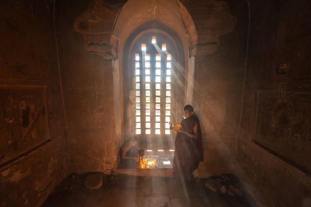Young buddhist novice monk reading in bagan myanmar.