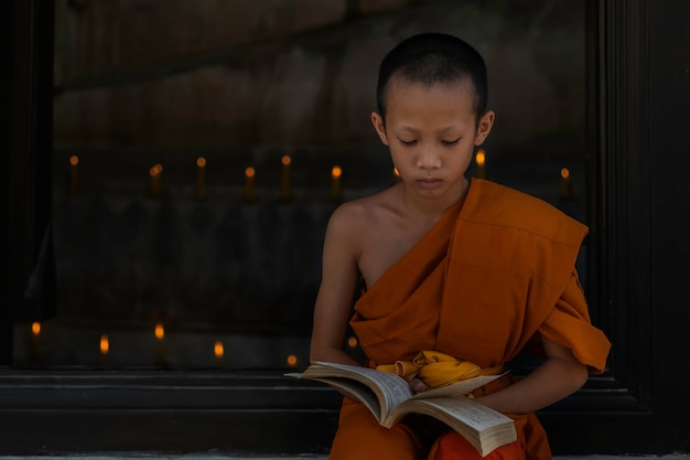 Young buddhist novice monk reading, young buddhist novice monk study inside monastery. asian young buddhist monk in one of the temples in thailand.