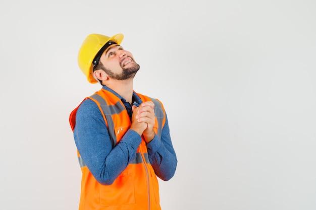 Молодой строитель, взявшись за руки в молитвенном жесте в рубашке