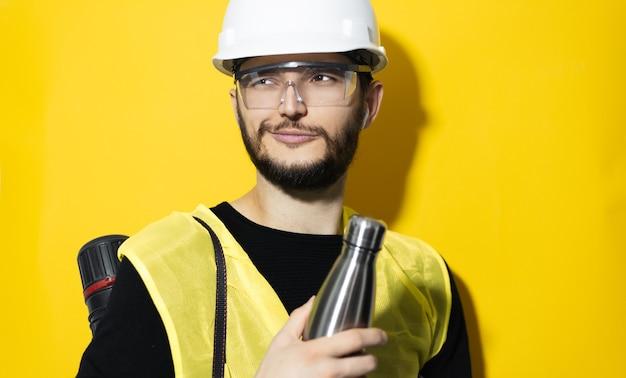 Молодой инженер-строитель с трубкой проектов, в строительном защитном шлеме и очках, с помощью беспроводных наушников, держащий стальную многоразовую термо-бутылку с водой на желтой стене.