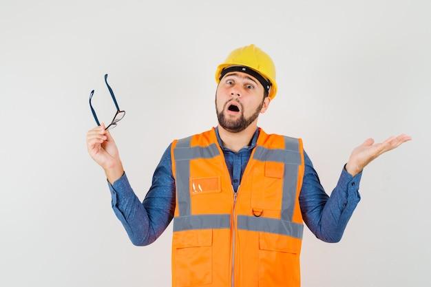 Молодой строитель держит очки в рубашке, жилете, шлеме и выглядит озадаченным.