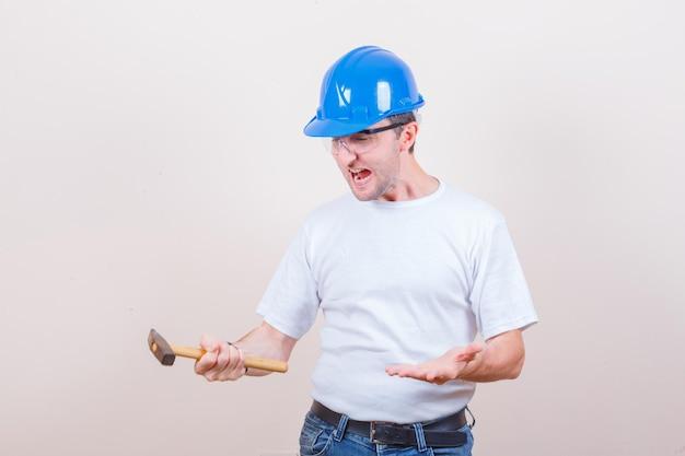 Tシャツ、ジーンズ、ヘルメットで叫びながらハンマーを保持している若いビルダー