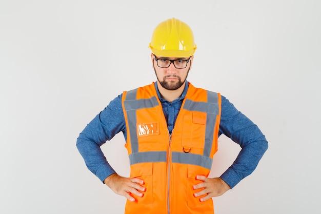 Giovane costruttore che tiene le mani sulla vita in camicia, gilet, casco e sembra serio. vista frontale.
