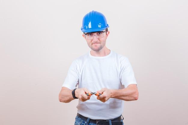 Giovane costruttore che tiene le pinze in maglietta, jeans, casco e sembra sicuro and