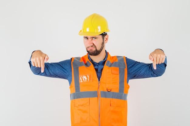 シャツ、ベスト、ヘルメットを着た若いビルダーが指を下に向け、不満を感じている、正面図。