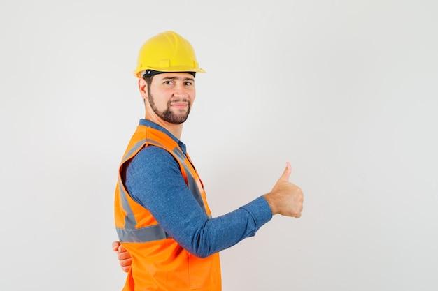 Молодой строитель в рубашке, жилете, шлеме показывает палец вверх и выглядит довольным.