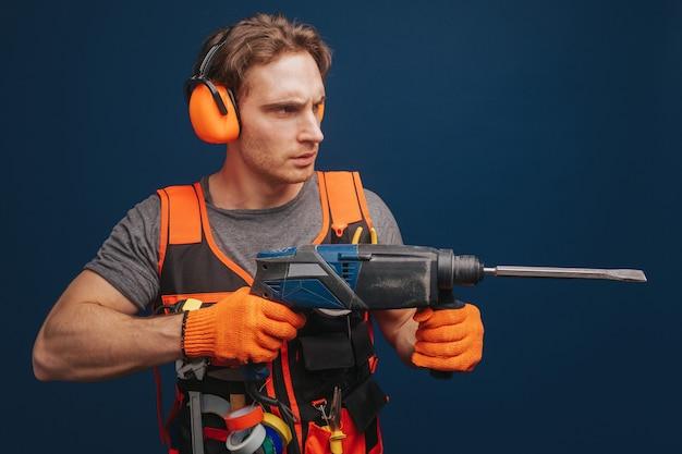 若いビルダーは真剣に銃のような装備を腕に持っています
