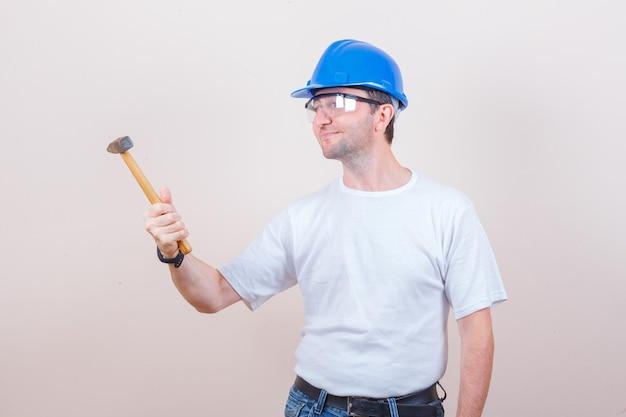Giovane costruttore che guarda il martello in maglietta, jeans, casco e sembra speranzoso