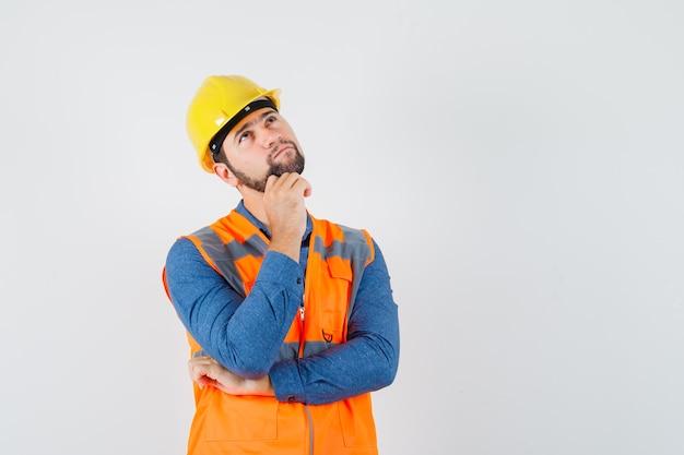 Giovane costruttore che osserva in su in camicia, gilet, casco e guardando pensieroso, vista frontale.