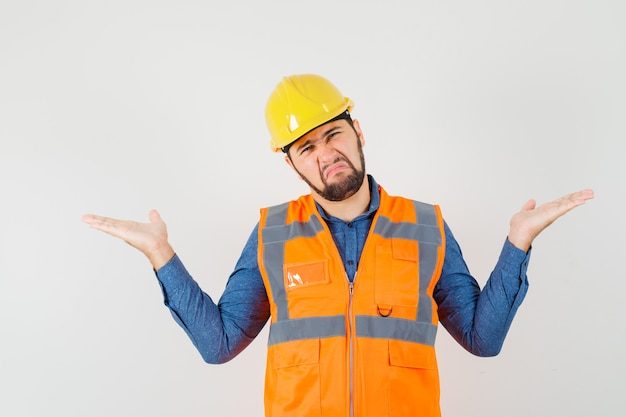 Young builder making scales gesture while scowling in shirt, vest, helmet front view.