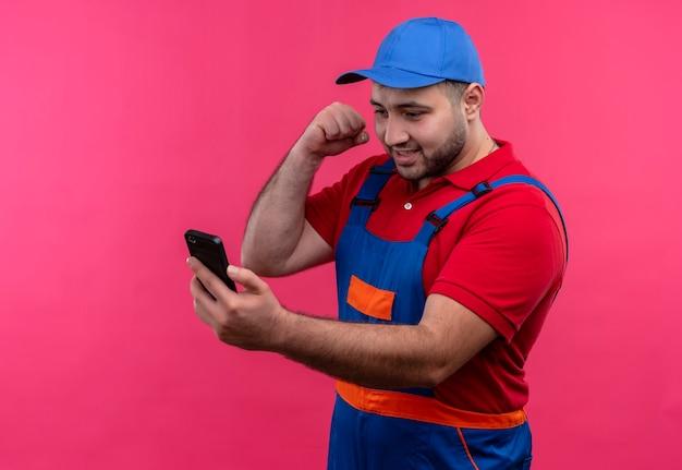 Giovane costruttore in uniforme da costruzione e berretto andando a pugni il suo cellulare arrabbiato e frustrato