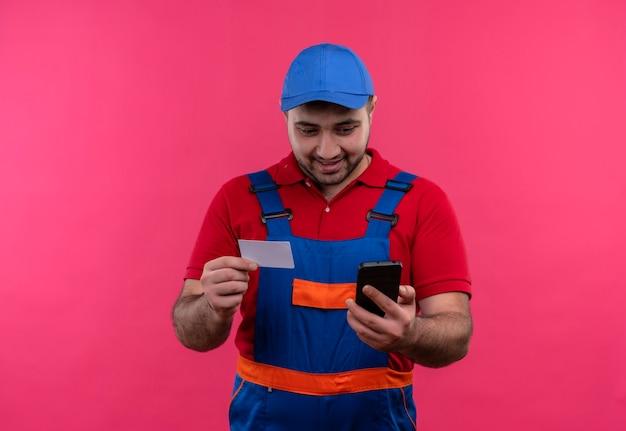 Uomo del giovane costruttore in uniforme da costruzione e cappuccio che tiene carta di promemoria guardando lo schermo del suo smartphone sorridente felice e positivo