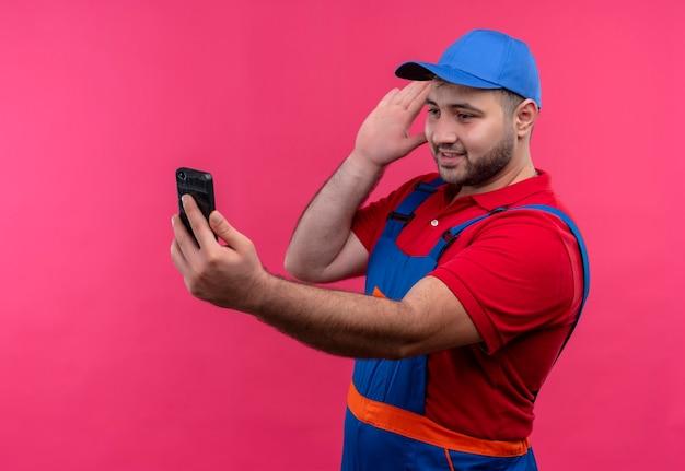 Uomo giovane costruttore in uniforme da costruzione e cappuccio che tiene lo schermo lookingat dello smartphone che si collega con qualcuno che fluttua con il saluto della mano