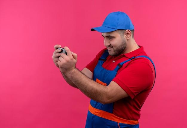 Uomo del giovane costruttore in uniforme da costruzione e cappuccio che tiene lo schermo lookingat dello smartphone che si collega con qualcuno