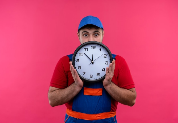 Giovane costruttore in uniforme da costruzione e berretto che tiene l'orologio da parete che nasconde il suo volto dietro di esso sbirciando sorpreso