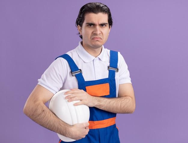 Uomo del giovane costruttore in uniforme della costruzione che tiene il suo casco di sicurezza che esamina l'espressione triste anteriore che fa la bocca ironica che sta sopra la parete viola