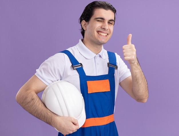 Uomo del giovane costruttore in uniforme della costruzione che tiene il suo casco di sicurezza che guarda anteriore con espressione fiduciosa che sorride che mostra i pollici in su che si leva in piedi sopra la parete viola