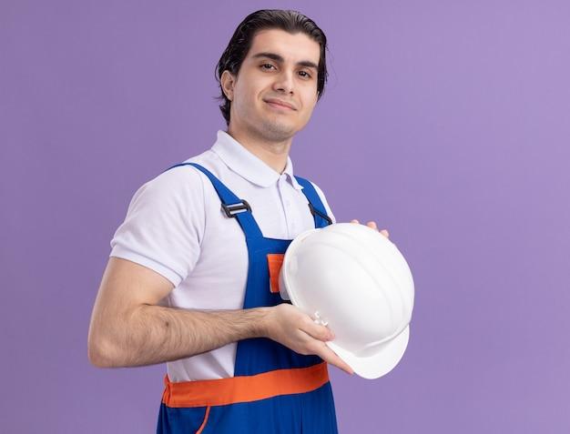 Uomo giovane costruttore in uniforme da costruzione che tiene il suo casco di sicurezza guardando la parte anteriore con espressione fiduciosa in piedi sopra la parete viola