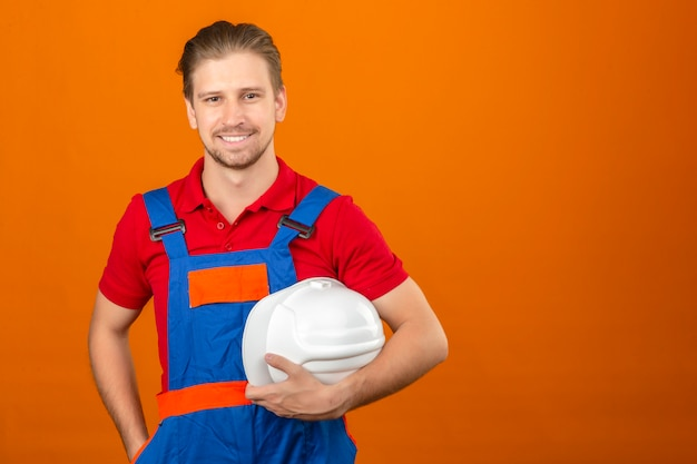 Young builder man in construction uniform holding safety helmet in hand with big smile on face standing over isolated orange wall with copy space